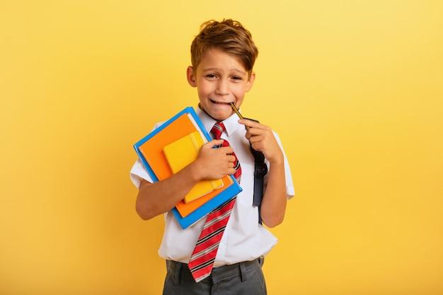 Kind huilt omdat hij veel huiswerk heeft. emotionele uitdrukking. gele achtergrond