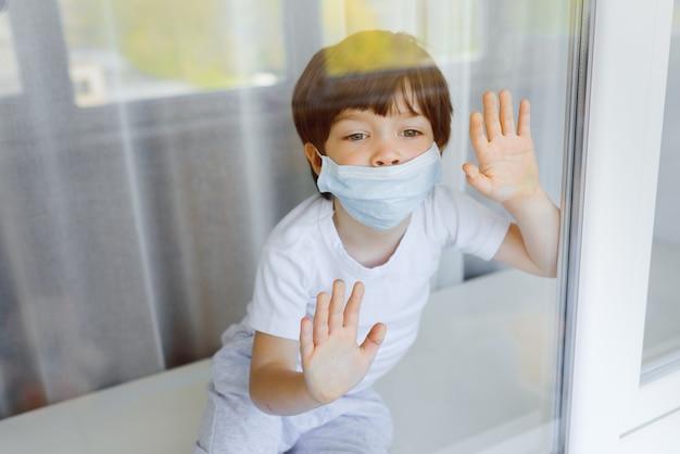 Kind in beschermend medisch masker kijkt uit het raam in de straat. blijf thuis