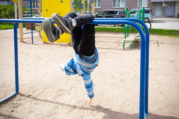 Kind in blauwe jas die ondersteboven aan dwarsbalken hangt in de speeltuin, tegen de achtergrond van huis en auto's.