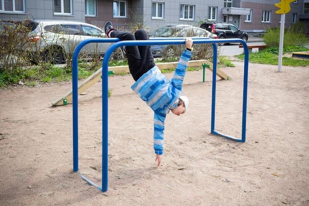 Kind in blauwe jas in speeltuin hangend aan tralies ondersteboven tegen de achtergrond van huis en auto's