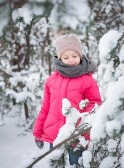 Kind in de winter. een klein meisje, buiten in de winter aan het spelen. een prachtig winters kinderportret. gelukkig kind, winterpret buiten.