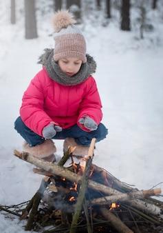 Kind in de winter. klein meisje in de winter in de natuur verwarmt haar handen bij het vuur