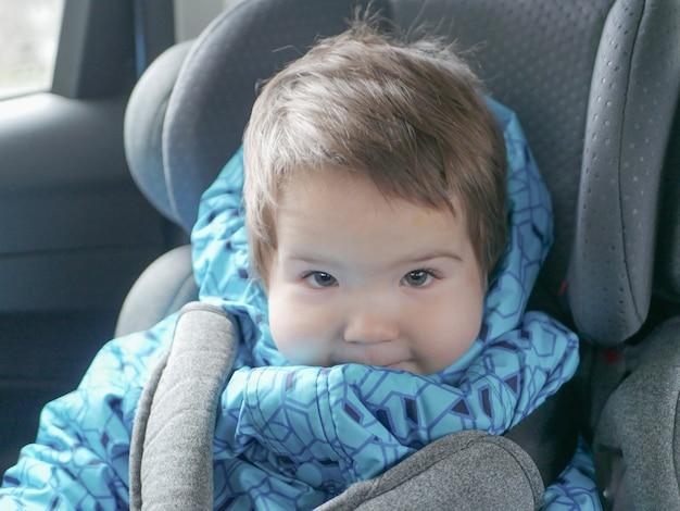 Kind in een autostoeltje. kinderveiligheid in de autostoel van het kind tijdens de slaap.
