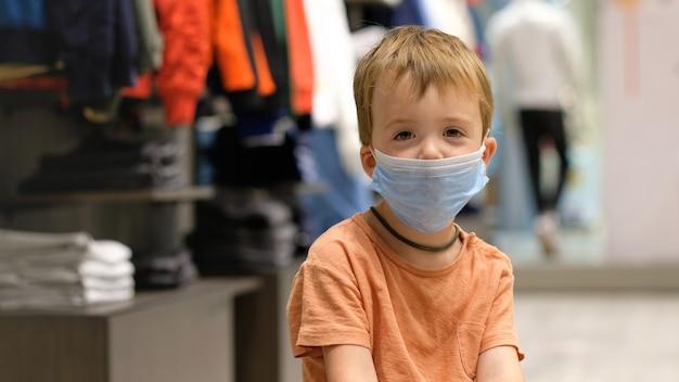 Kind in een beschermend masker in een winkel