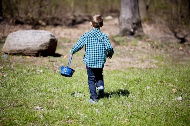 Kind in een blauw flanellen overhemd dat een mand vasthoudt en door een veld in het zonlicht loopt