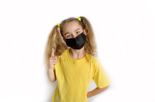 Kind in een geel shirt met een zwart masker van covid op een witte achtergrond. hoge kwaliteit foto