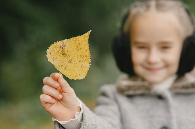 Kind in een herfstpark. kid in een grijze jas.
