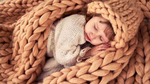 Kind in een hoed onder een deken van natuurlijke schapenwol. merino plaid brei dekt meisje. designer hoeden natuurlijk wolgaren.