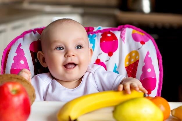 Kind in een hoge stoel eten fruit en glimlachen
