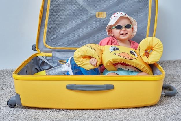 Kind in een koffer met spullen voor een vakantie aan zee of vakantiereizen. kopieer ruimte.