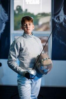 Kind in een schermpak met een zwaard in de hand in de studio. jonge meisjes oefenen en oefenen schermen. sport, gezonde levensstijl.