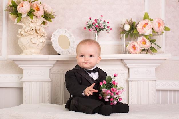 Kind in een smoking zittend op het bed naast de open haard met bloemen in hun handen.