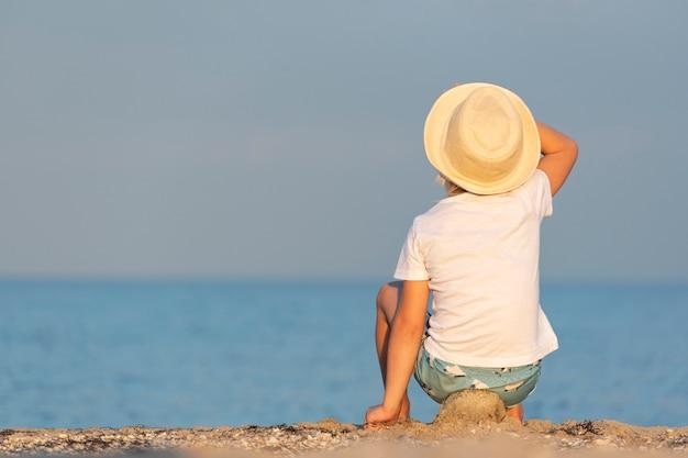 Kind in een strooien hoed zittend op het strand en kijken naar zee