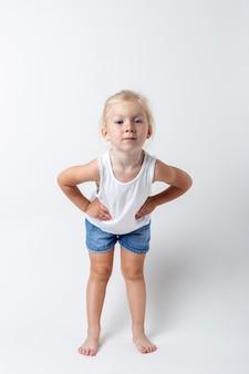 Kind in een t-shirt, korte broek in de studio op een lichte achtergrond.