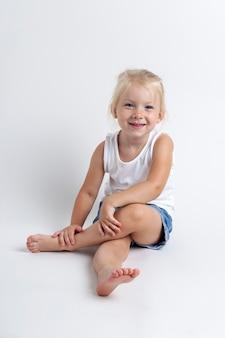 Kind in een t-shirt, korte broek zittend in de studio op een lichte achtergrond.