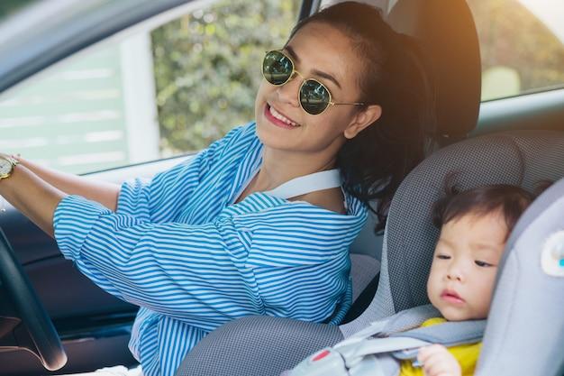 Kind in een veiligheidszetel dichtbij aan moeder die op het voorwaarts zitten van de auto zit. autoverzekering