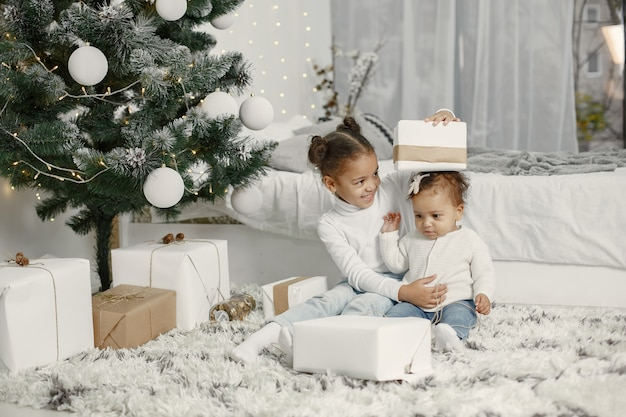 Kind in een witte trui. dochters stitting in de buurt van de kerstboom. twee zussen thuis.