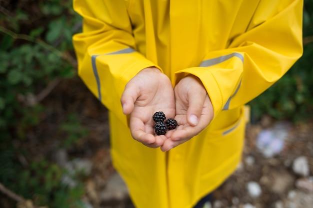 Kind in geel jasje met bramen in zijn handen