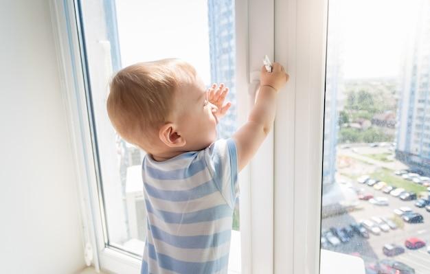 Kind in gevaar. babyjongen die aan de hendel van het raam trekt
