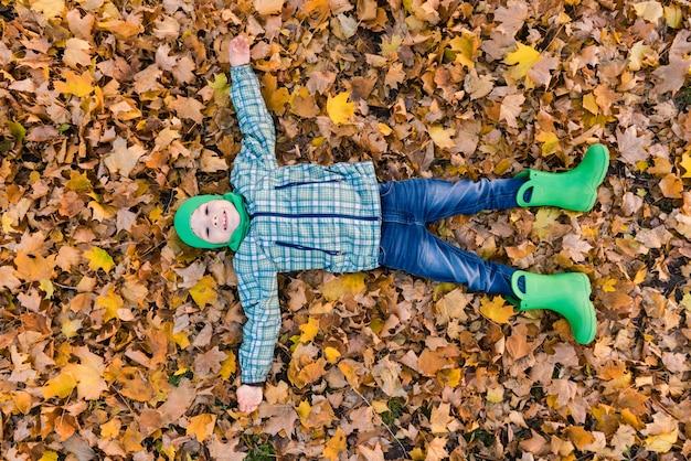 Kind in groene hoed en rubberlaarzen in de herfstpark. de gelukkige jongen lag op het esdoornblad. uitzicht van boven.