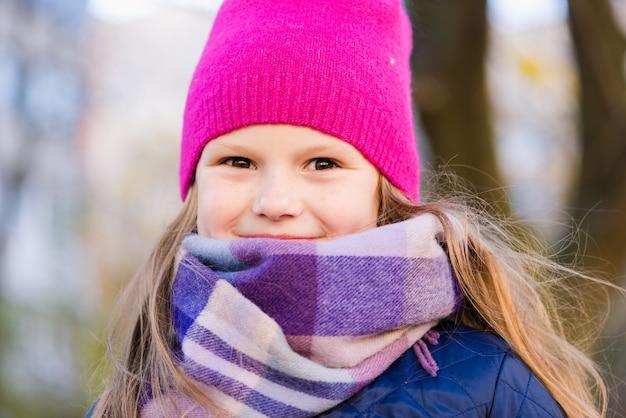 Kind in grote sjaal en felroze hoed close-up. herfst portret van gelukkig meisje basisschool.
