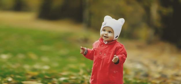 Kind in herfstgebladerte zet zijn eerste stapjes