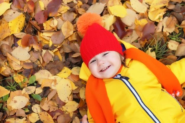 Kind in herfstpark dat in bladeren ligt en glimlacht