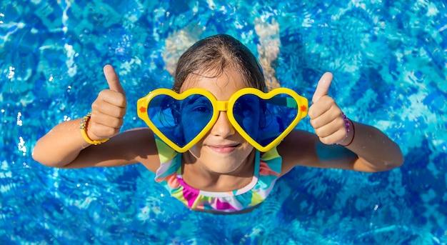 Kind in het zwembad met een grote bril. selectieve aandacht.