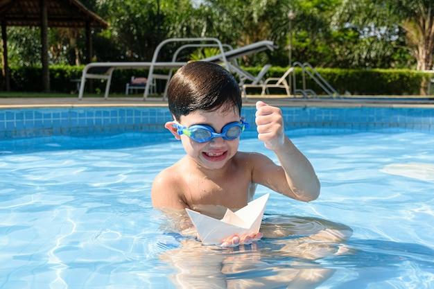 Kind in het zwembad, met gesloten vuist, gaat de papieren boot vernietigen.