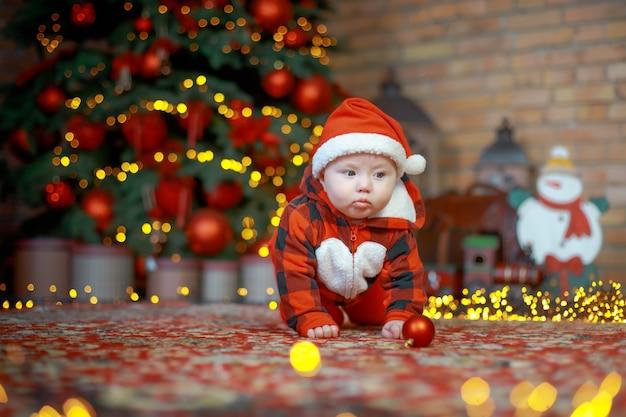 Kind in kerstmankostuum bij een nieuwjaarsboom op kerstavond gelukkig nieuwjaar 2022 concept