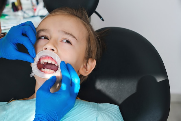 Kind in kliniek die tandheelkundige behandeling doet tandartsorthodontie bang kind op tandartsstoel