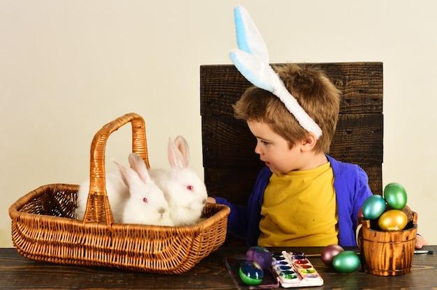 Kind in konijntjesoren op paasdag. leuke jongen met easterskonijn in mand en eieren.