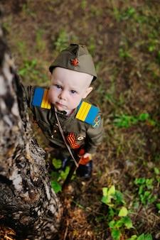 Kind in militair uniform in de natuur