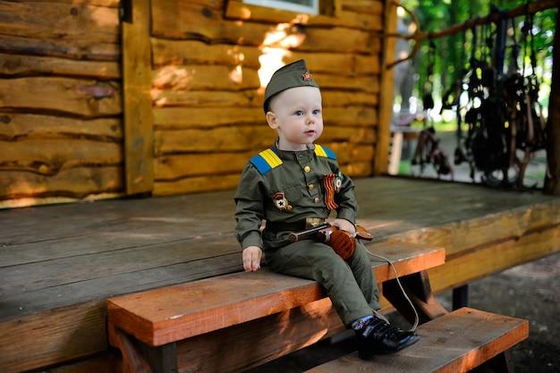 Kind in militair uniform tegen de achtergrond van de natuur