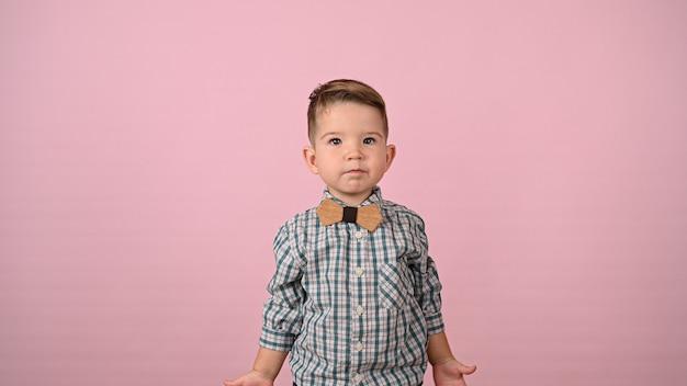 Kind in overhemd en vlinderdas, op een roze achtergrond. hoge kwaliteit foto
