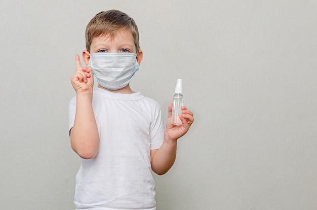 Kind in quarantaine vanwege een pandemie (epidemie) van het coronavirus. een jongen met een beschermend medisch masker heeft een ontsmettingsmiddel in zijn handen.