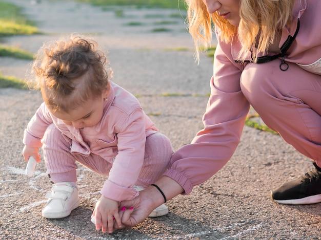 Kind in roze kleding en moeder tekenen