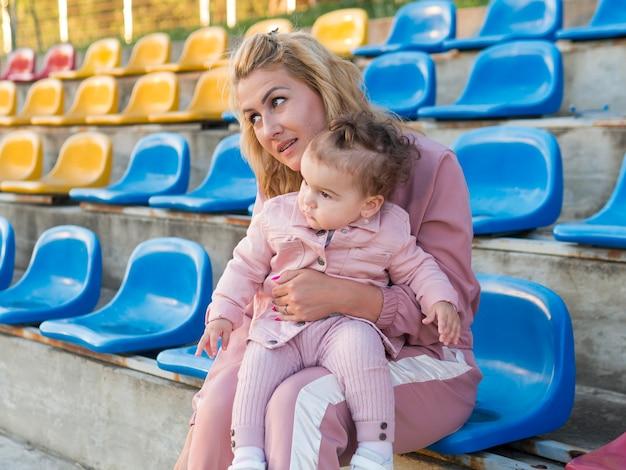 Kind in roze kleding en moeder zittend op een stoel