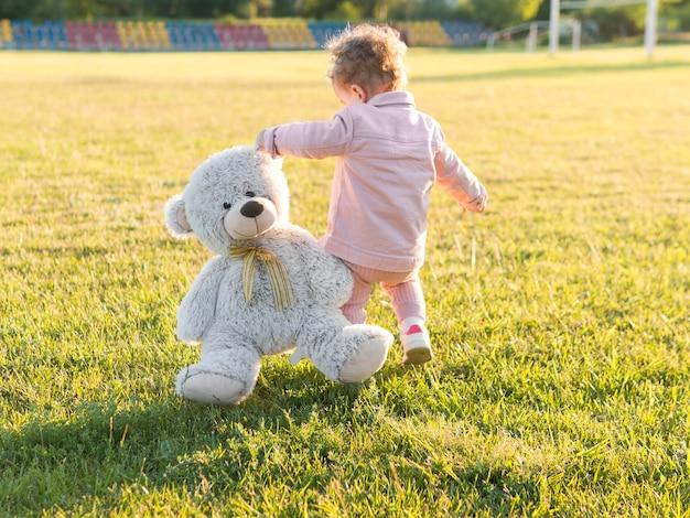 Kind in roze kleren en zijn vriendelijke speelgoed