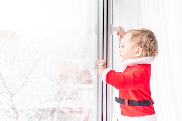 Kind in santa-pak op de vensterbank van het raam, het concept van nieuwjaar en kerstmis