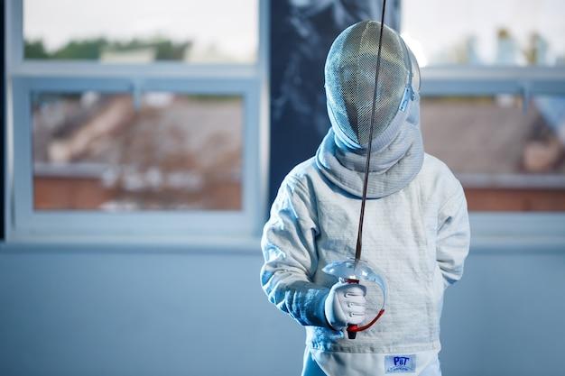 Kind in schermkostuum en masker, met zwaard, schermschool