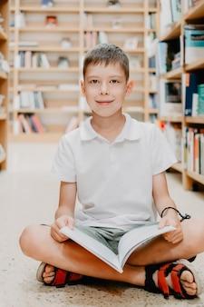 Kind in schoolbibliotheek. kinderen lezen boeken. kleine jongen lezen en studeren. kinderen bij boekhandel. slimme intelligente voorschoolse jongen die boeken kiest om te lenen.