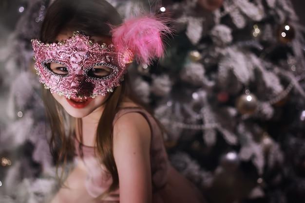 Kind in slimme kleren voor de kerstboom. oudjaarsavond. wachten op het nieuwe jaar.