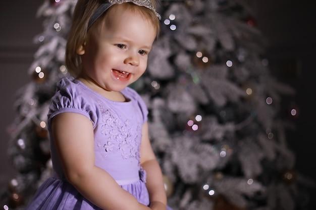 Kind in slimme kleren voor de kerstboom. wachten op het nieuwe jaar.