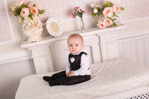 Kind in smoking, zittend op het bed naast de open haard. de bruidegom.