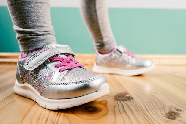 Kind in sneakers op houten oppervlak