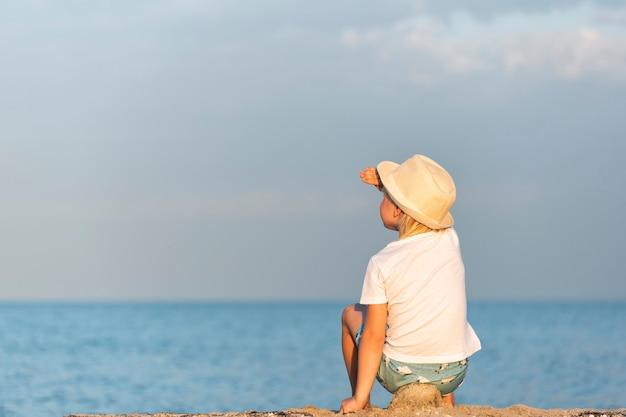 Kind in strooien hoed zittend op het strand en kijkt naar zee