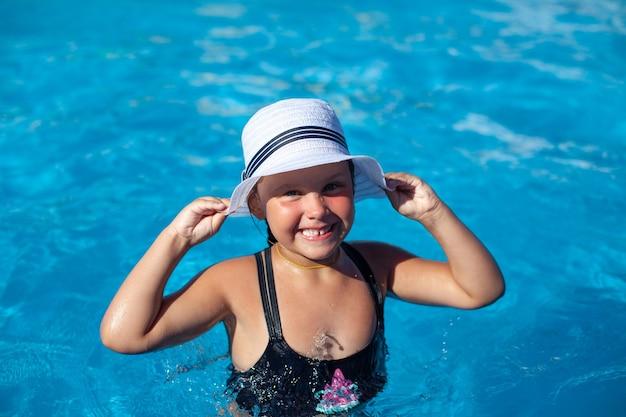 Kind in wit panama geniet van de zomer, een klein gelukkig gebruind meisje in een zwarte zwembroek staat in het water...