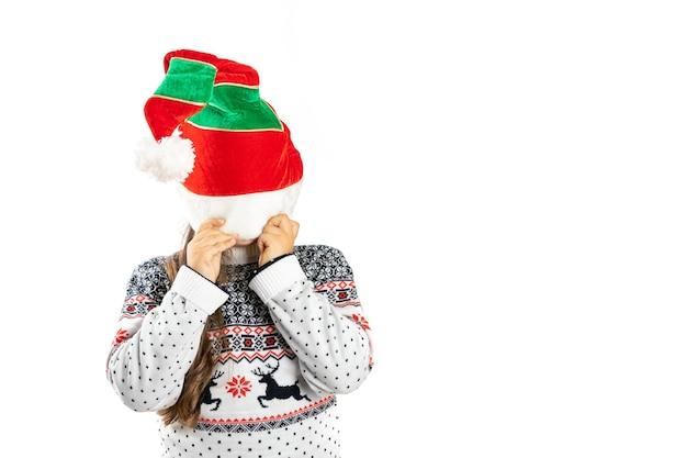 Kind in witte gebreide kersttrui met rendieren verbergen gezicht onder dwerg hoed geïsoleerd op witte b...