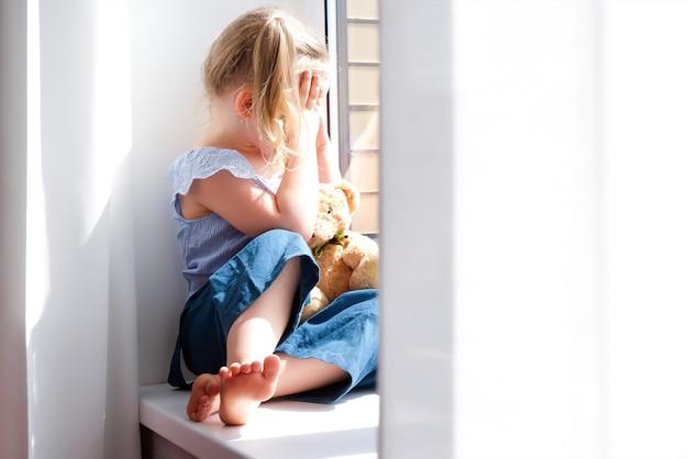 Kind is een meisje alleen thuis. meisjes zitten op de vensterbank en kijken huilend uit het raam.